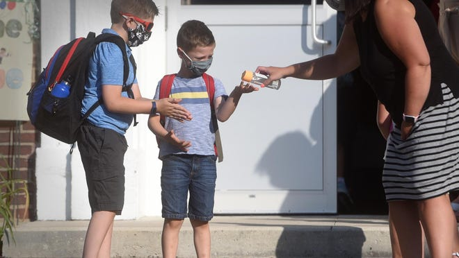 Students get hand sanitizer before they enter Maple Street Magnet School in Rochester on the first day back at school Tuesday. The school is the first in the state to reopen for in-person learning amid the coronavirus pandemic, according to the New Hampshire Department of Education.