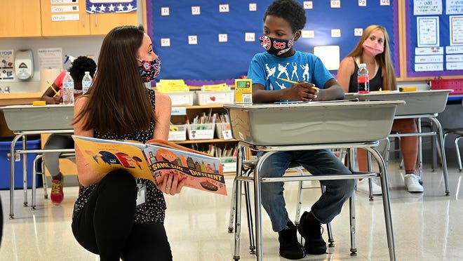 Keeping her distance, first-grade teacher Catherine Manos shows a page in a book to Joshua Birch, an incoming fifth-grader, during a simulated school day Friday at Brookside Elementary School in Milford.