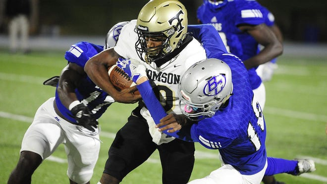 Taymarion Martin of Thomson, center, runs as Burke County defenders Jaedon Middleton, left, and Kohen Rogers close in to make the tackle at the high school football game between Burke County and Thomson on October 30, 2020 in Waynesboro, Ga.