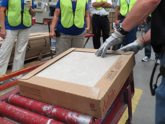 Dickson visitors look at tile rolling off the line at the Dal-Tile plant in Oklahoma.