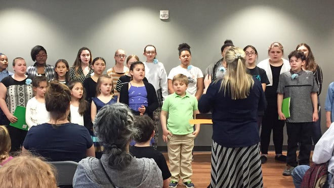 Educator Amy Phillips conducts the Nesin Cultural Arts Children's Choirs at an outreach concert at the Ethelbert B. Crawford Public Library in Monticello in  2019.