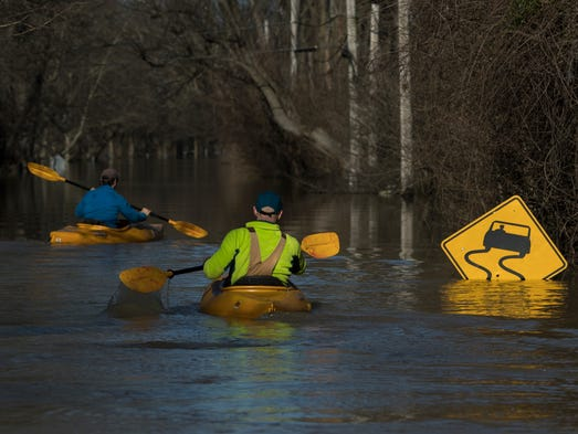 Kayakers make their way down River Road in Louisville,