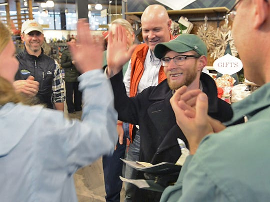 L.L. Bean staff celebrate a $500 gift card winner after doors opened at the new store on Cherry Street in Burlington Friday morning.