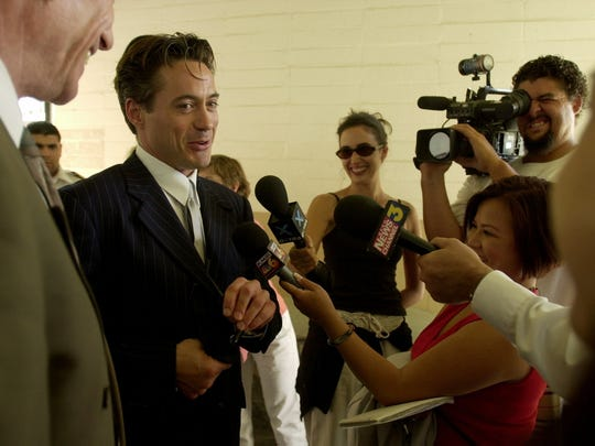 Robert Downey Jr. (left) smiles as he answers questions from the media after the judge agreed to drop his parole status with Riverside County at the courthouse in Indio. Downey completed his drug treatment under Prop 36.