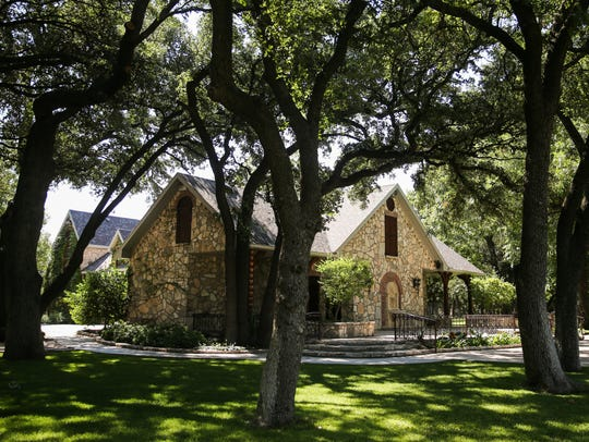 A wedding chapel is nestled in trees near rows of vines