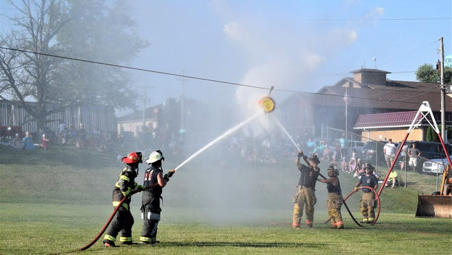 Firefighters from Apple Creek (left) faced off against members of Western Holmes Fire District Team 2 in the opening round of the water barrel blast during the East Holmes Firemen's Festival Saturday at Berlin Elementary School.
