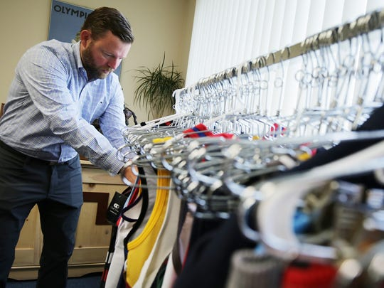 Tom Keen shows some of the wrestling singlets that his company Cliff Keen Athletics in Ann Arbor makes on Oct. 29.
