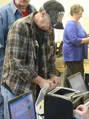 An early voter at the Grinnell voting station at the Drake Library goes through the process to get his ballot for the 2016 presidential election.