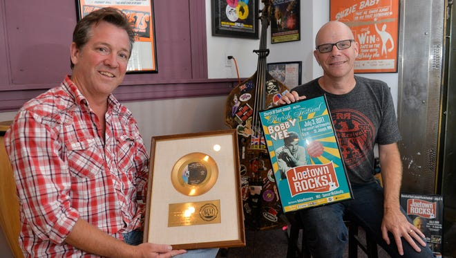 Bobby Vee's sons, Jeff Velline and Tommy Velline, hold gold records and posters Tuesday, Aug. 30, 2016, amid the plethora of memorabilia at the family business, Rockhouse Productions in St. Joseph.