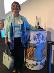 Judy Terry poses with a decorated rain barrel at an