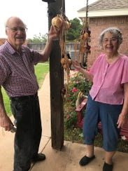 Margie and Charles G. Anderson Sr. hang ripe onions