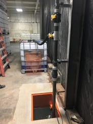 Inside the Cornell Street plant in Milwaukee, inspectors photographed a tote used to collect wastewater and a nearby drain.