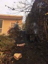 A resident waters down his smoldering lawn the day