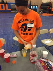 Megan Sooy, a student at Millville High School, pours