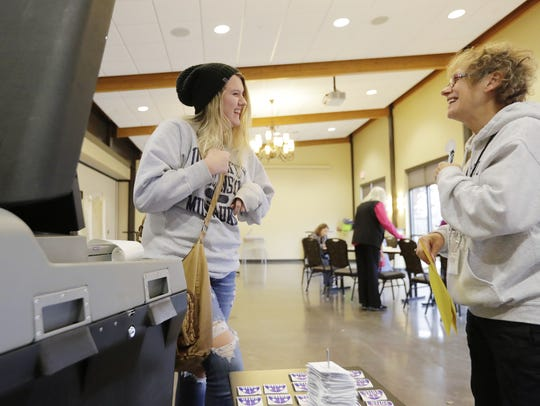 First-time voter Tia Beauleau, left, laughs with polling