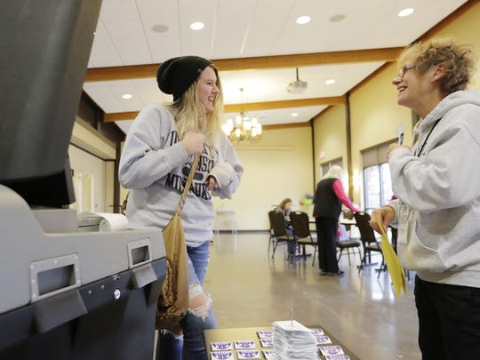 First-time voter Tia Beauleau, left, laughs with polling site worker Gail Rudnick after casting her ballot at the Green Bay Botanical Garden.