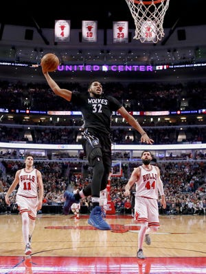 Minnesota Timberwolves' Karl-Anthony Towns (32) goes up for a dunk as Chicago Bulls' Doug McDermott (11) and Nikola Mirotic watch during the second half of an NBA basketball game Tuesday, Dec. 13, 2016, in Chicago.
