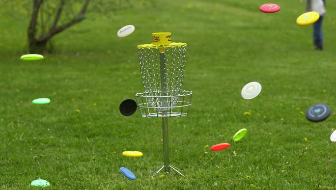 Disc golfers aim for the basket on a course in Parma.