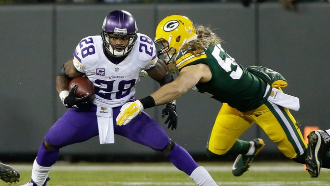 Green Bay Packers inside linebacker Clay Matthews (52) wraps up Minnesota Vikings running back Adrian Peterson (28) in the first quarter.