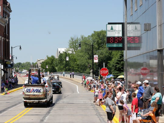 Parade floats and cars approach the Grand Avenue bridge in downtown Wisconsin Rapids during the Cranberry Blossom Festival Parade, June 19, 2016.