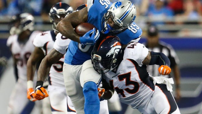 Lions tight end Eric Ebron makes a catch against Broncos safety J.T. Ward during the fourth quarter Sunday at Ford Field.