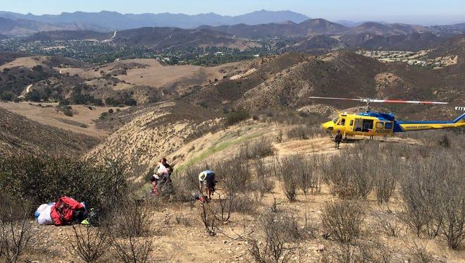 A Ventura County helicopter crew helps with the rescue Saturday of an injured paraglider operator.