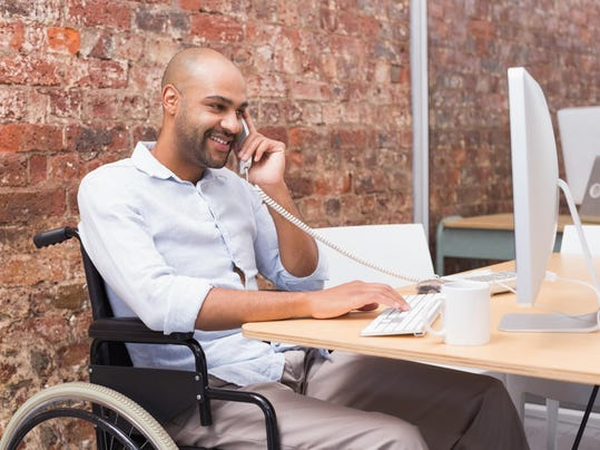 Businessman in wheelchair working at his desk on the phone