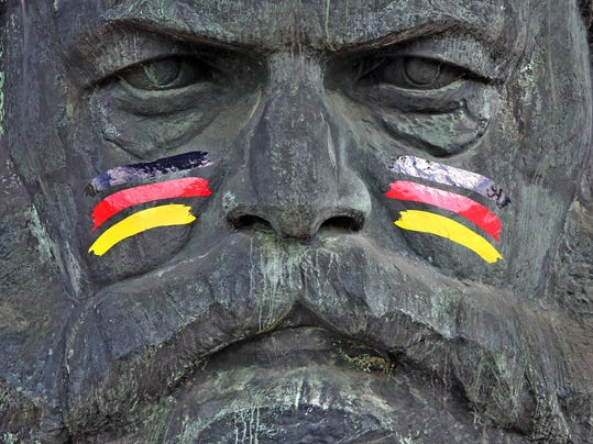 The monument of German philosopher, economist, and revolutionary socialist , Karl Marx, is painted with German national colors  as advertisement  for the upcoming soccer World Cup tournament in Brazil, in Chemnitz, eastern Germany, Friday June 6, 2014.    (AP Photo/dpa,Jan Woitas)