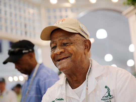 Long-time Pinehurst caddie Willie McRae signs autographs in the merchandise tent during the second round of the U.S. Open golf tournament in Pinehurst, N.C., Friday, June 13, 2014. McRae, 81, has  been caddying at Pinehurst since he was 10, and has caddied for some of the greats of the game as well as four presidents. (AP Photo/David Goldman)