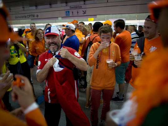 A Chile soccer fans jokes around with Dutch soccer fans at a subway station on their way to the World Cup group B match between Chile and the Netherlands at the Itaquerao stadium in Sao Paulo, Brazil, Monday, June 23, 2014. Both teams having already qualified for the round of 16, Monday's match will decide which of them wins Group B. (AP Photo/Dario Lopez-Mills)