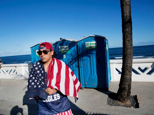 A fan of the U.S. national soccer team walks by the seaside with a U.S. flag draped over his shoulders, in Salvador, Brazil, Monday, June 30, 2014. Salvador is one of the host cities of the FIFA 2014 Soccer World Cup. (AP Photo/Rodrigo Abd)