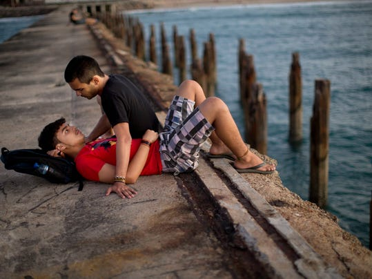 A couple spends time on an abandoned pier in Fortaleza, Brazil, Wednesday, July 2, 2014. Fortaleza is one of many cities hosting World Cup soccer matches this month. (AP Photo/Rodrigo Abd)