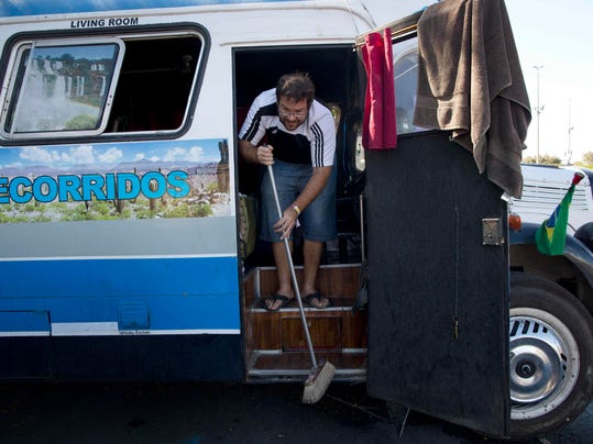 """In this Sunday, July 6, 2014 photo, Argentine Jose Ribeti, 29, sweeps the stairs of his bus """"Carnavalito,"""" in the Granja do Torto parking lot used by traveling World Cup soccer fans as a campground, in Brasilia, Brazil. Ribeti is part of a group of Argentine men who has spent the last month traveling all over Brazil in a converted bus to watch their national soccer squad's progress during the World Cup. (AP Photo/Rodrigo Abd)"""