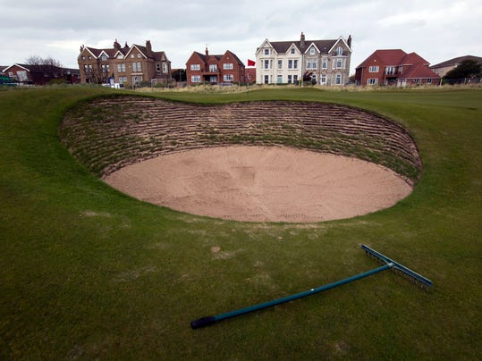FILE - In this April 23, 2014, file photo, a rake rests next to a bunker on the first hole at Royal Liverpool Golf Club in Hoylake, England. The British Open golf championship begins on Thursday July 17, 2014. (AP Photo/Jon Super, File)