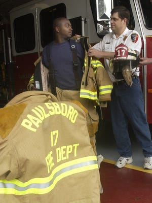 2003 file photo: Paulsboro Fire Dept. gets new gear. Fireman Donnie Montgomery is helped with a jacket by Fire Chief Gary Stevenson.