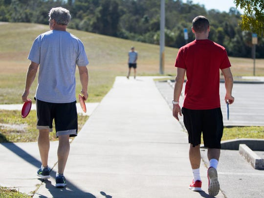 Mike Mast and Mike Matrisciano prepare for Tuesday's round of disc golf.