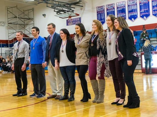 Players and coaches from the 2004 St. Clair High School girls basketball team line up after receiving their Athletic Hall of Fame medals at St. Clair High School Feb. 2. The team, coached by Sandy Rutledge and Shawn Sharrow and assisted by Bill Westerhof, was the first girls basketball team to reach the state finals.