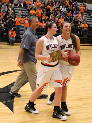 Walnut Grove junior Bayley Harman, center, and senior Raylie Hejna, right, accepted a district championship plaque and game ball from Willard athletic director Jeff Staley, left, after Walnut Grove won the 2017 Class 1 District 5 basketball championship.