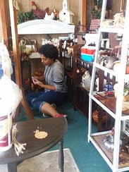 Shawnna Apley, 15, stocks her section of a local store
