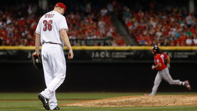 Cincinnati Reds relief pitcher Blake Wood (36) walks back to the mound after giving up a grand slam to Washington Nationals' Anthony Rendon, right, in the seventh inning of a baseball game, Saturday, July 15, 2017, in Cincinnati.