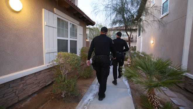 Officer Christopher Tooth (far left) and Officer Greg Elias walk to their vehicles after tending to a 911 phone call on Tuesday, December 29, 2015, in Desert Hot Springs, Calif.