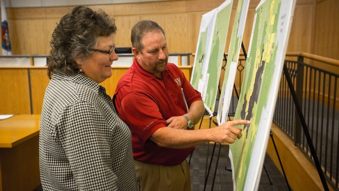 Janine Divyak, chief planner for Doña Ana County, and Scott Eschenbrenner, New Mexico State University special assistant to the president, look at an official zoning map of the county after a planning and zoning committee meeting at county offices, Thursday, Aug. 11, 2016.