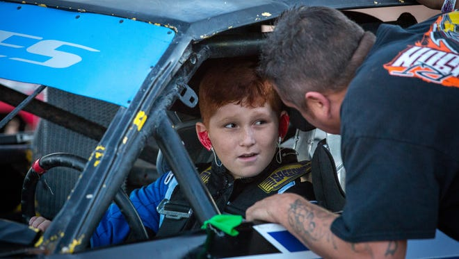 """Eleven-year-old race car driver Aasa """"Boo"""" Flores gets advice from his father Larry Flores before the start of a recent race at the Southern New Mexico Speedway west of Las Cruces."""