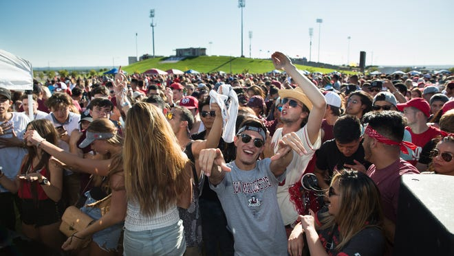 NMSU and UNM students dance and cheer as a disk jockey plays music on Saturday, September 10, 2016, during the NMSU UNM tailgate.