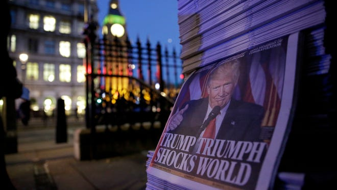 Copies of the London Evening Standard newspaper report on President-elect Donald Trump winning the American election, backdropped by the Houses of Parliament in London, Wednesday, Nov. 9, 2016.  Republican candidate Trump secured victory in Tuesday's U.S. presidential election.