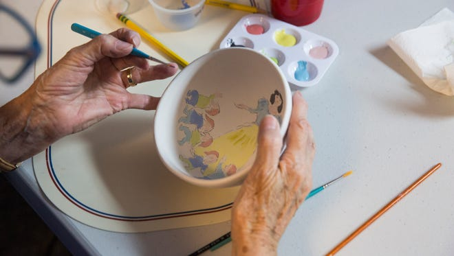 Liz Eflin works on painting a bowl with a depiction of Snow White and the Seven Dwarfs during a bowl painting session at the Meals of Hope warehouse in Naples on Thursday, Jan. 18, 2018.