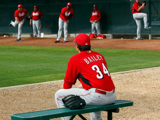 Reds starting pitcher Homer Bailey watches his teammates