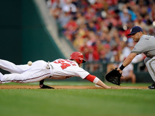 Washington Nationals' Bryce Harper (34) dives back safely to first on a pickoff attempt as Milwaukee Brewers first baseman Mark Reynolds (7) awaits the ball during the second inning of a baseball game, Friday, July 18, 2014, in Washington. (AP Photo/Nick Wass)