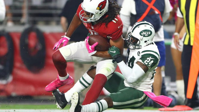 Jets cornerback Darrelle Revis (24) tackles Cardinals wide receiver Larry Fitzgerald during a game in October 2016. Both players were named to the NFL's 2010s All-Decade Team.