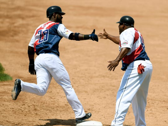 Melky Mesa gets a high-five from first base coach Sandy